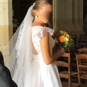 LAURE - Robe en organza et guipure avec empiècement à la taille et décolleté plongeant en V devant et inversé dans le dos. Petites manches à volant. La mariée portait un voile de famille restauré par nos soins.