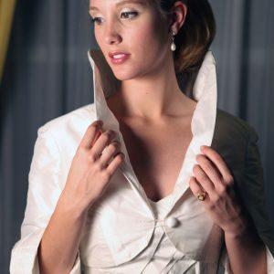 ARIELLE - Robe de mariée en doupion de soie, bustier corseté avec plissage asymétrique en cache-coeur, traîne partant de deux plis creux et veste avec grand col rond. Voile en tulle bordé de dentelle.