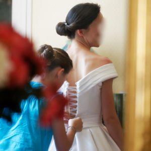 BENEDICTE - Robe corseté en mikado avec décolleté sur les épaules, revers plissé comme la ceinture et jupe à plis creux. Voile de famille restauré par nos soins.