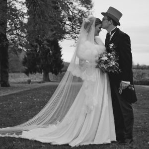 ASTRID - Robe en crêpe de soie et dentelle de calais, taille basse avec décolleté sur les épaules et jupe trapèze. Voile en tulle bordé de dentelle de calais.