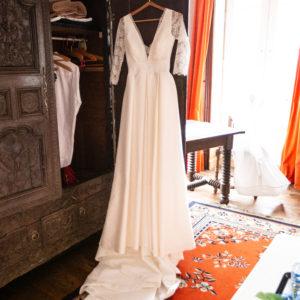 DELPHINE - Robe en mikado soie et coton et dentelle de calais. Manches 3/4, décolleté en pointe de vante et carré dans le dos bordé d'un galon de dentelle. Entièrement à la taille et jupe à plis creux.
