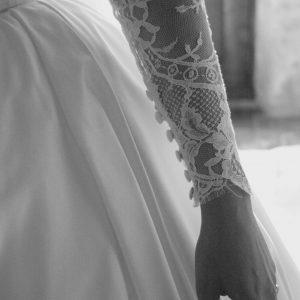 AMICIE - Robe corsetée en satin duchesse de soie et dentelle de calais. Traîne amovible boutonnée jusqu'à l'ourlet et manches en dentelle également boutonnées. Voile à l'ancienne en point d'esprit et dentelle de calais brodé à la main.