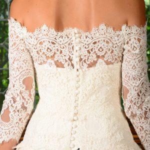 Boléro en dentelle de calais rebrodée, épaules nues, manches 3/4. Fermeture à boutons dans le dos avec brides fixées sur les boutons de la robe.