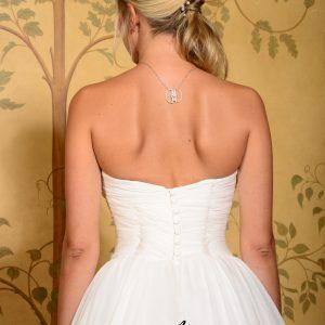 MODELE VILLANDRY -  Robe de mariée bustier corsetée en mousseline de soie et doublée en pongé de soie. Travail de drapé sur le buste avec décolleté en coquillage. Tombé de jupe en cascade, laçage intérieur et boutonnage extérieur. Etole amovible nouée dans le dos.