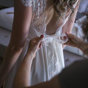 SARAH - Robe fluide en crêpe de soie avec un grand dos nu et application de dentelle de calais. Petits boutons en perle.