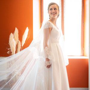 AURORE - Robe de mariée en mikado, jupe à plis creux, décolleté V devant et rond dans le dos avec détail de guipure et manches courtes en guipure. Ceinture brodé et voile de 3,5 mètre en tulle bordé de dentelle de Calais.