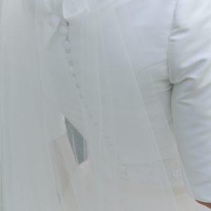 Veste courte en mikado, encolure bateau avec col montant noué dans le dos. Fermeture à boutons dans le dos et brides fixées aux boutons de la robe. Manches 3/4.