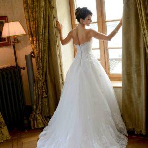 DANIA - Robe de mariée en tulle de soie et dentelle rebrodée. Bustier corseté et drapé en tulle avec application de dentelle. Boléro en dentelle rebrodée. Voile en tulle bordé de dentelle rebrodée.
