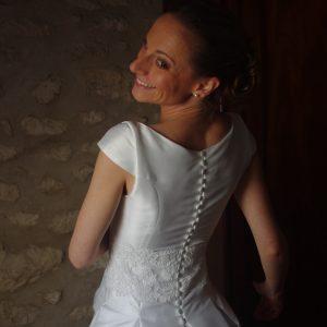VERONIQUE - Robe de mariée en mikado, le bas s'ouvrant sur des plis creux, ceinture en dentelle rebordée, traîne amovible en organza de soie et petite veste avec boutonnage dans le dos et col fermant avec un noeud. Voile en tulle bordé de dentelle rebrodée.